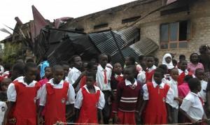 Kinder vor dem abgebrannten Gebäuden
